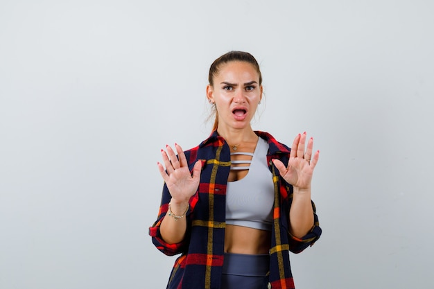 Young lady raising hands in surrender gesture in top, plaid shirt and looking perplexed. front view.