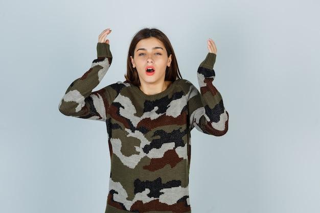 Giovane donna alzando le mani in maglione, gonna e guardando perplesso