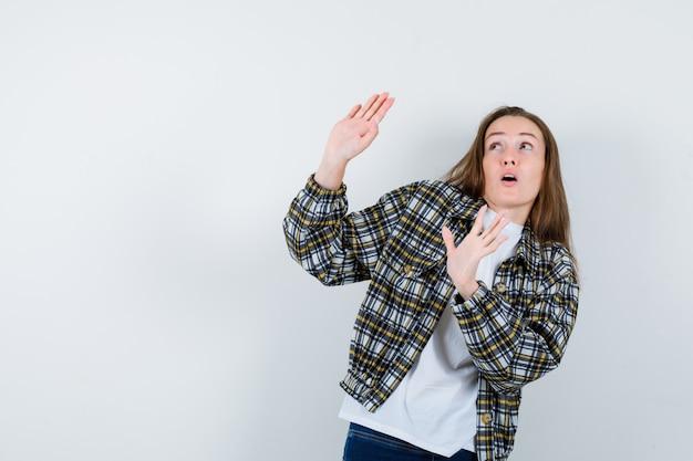 Tシャツ、ジャケット、怖い顔、正面図で身を守るために手を上げる若い女性。
