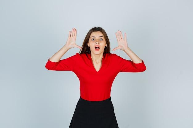 赤いブラウス、スカート、恐ろしい顔で誰かを怖がらせるために手を上げる若い女性