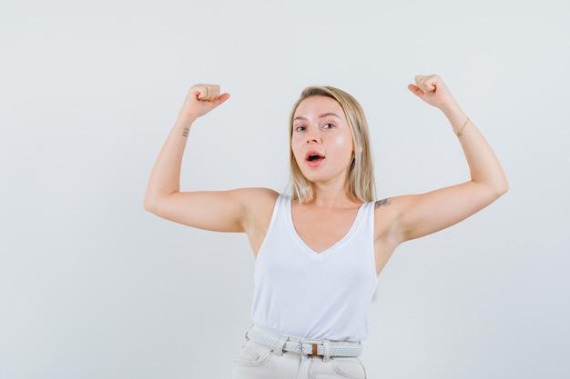 Giovane donna che alza le braccia per mostrare il suo potere in camicetta bianca e sembra flessibile