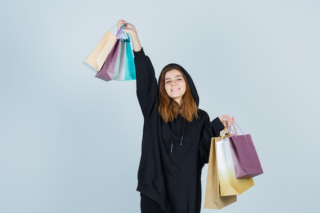 Девушка поднимает пакеты, позирует в огромной толстовке с капюшоном, штанах и выглядит энергичной, вид спереди.
