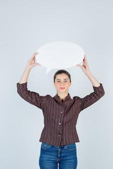 シャツ、ジーンズ、満足そうに見える、正面図で紙のポスターを上げる若い女性。