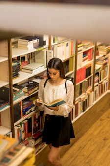 Young lady reading book near shelf