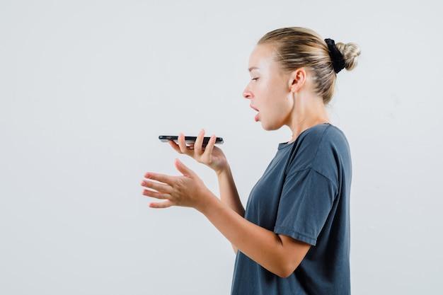 灰色のtシャツで携帯電話にボイスメッセージを録音する若い女性。