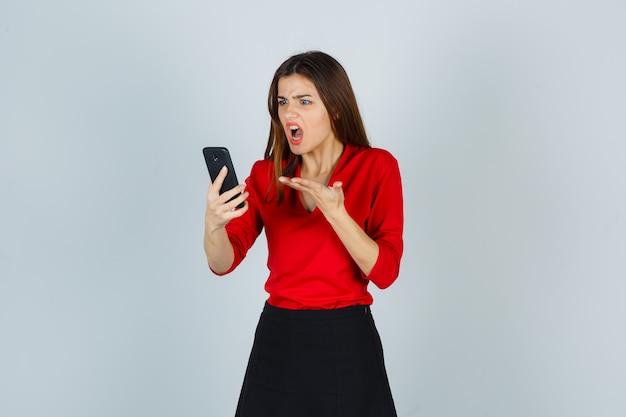 빨간 블라우스에 휴대 전화에 음성 메시지를 녹음하는 젊은 아가씨