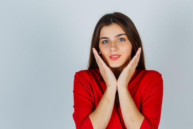 Giovane donna in camicetta rossa che tiene le mani sotto il mento e che sembra carina