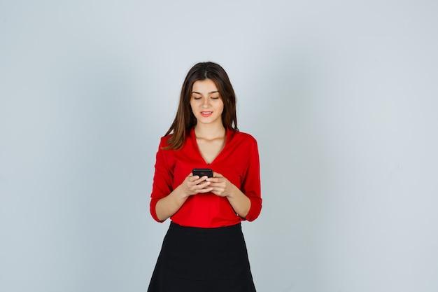 Giovane donna in camicetta rossa, gonna in chat sul cellulare e sembra felice