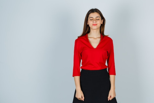 Young lady in red blouse, skirt closing eyes and looking hopeful