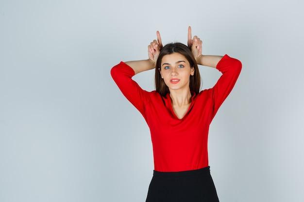Giovane donna in camicetta rossa, gonna che tiene le dita sopra la testa come corna e sembra carina
