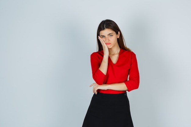 Young lady in red blouse, skirt holding hand on cheek and looking gloomy