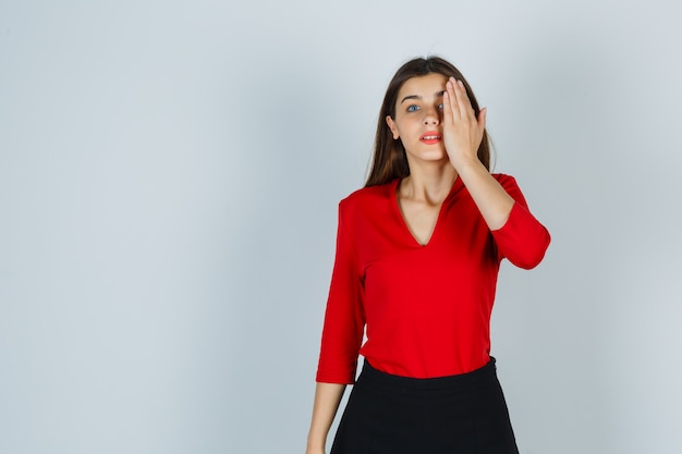 Giovane donna in camicetta rossa, gonna che tiene la mano sugli occhi e sembra seria