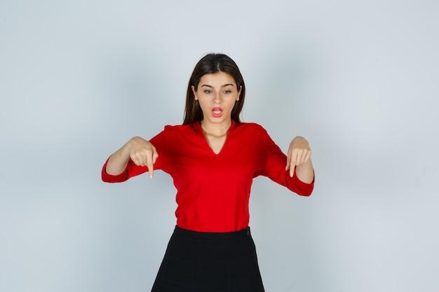 Giovane donna in camicetta rossa, gonna rivolta verso il basso e con aria perplessa