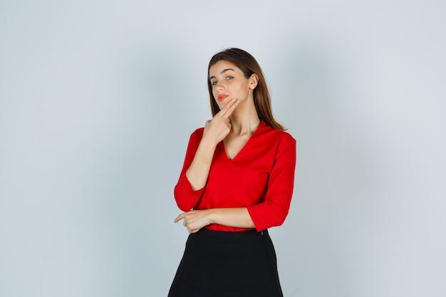 Giovane donna in camicetta rossa, gonna in posa tenendo le dita sul mento e guardando carino