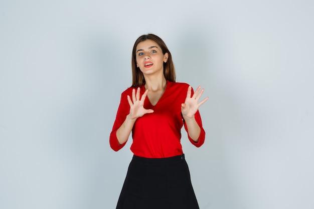 Giovane donna in camicetta rossa, gonna che mostra le palme in gesto di resa e sembra felice