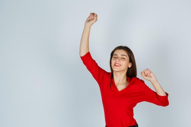 Giovane donna in camicetta rossa, gonna che mostra il gesto del vincitore e sembra beata