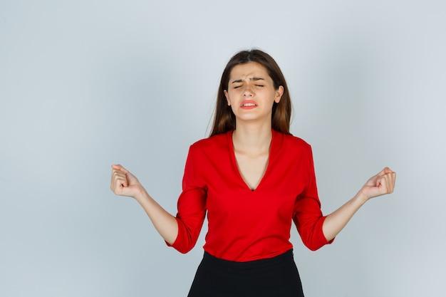 Giovane donna in camicetta rossa, gonna che mostra il gesto del vincitore e sembra fortunata