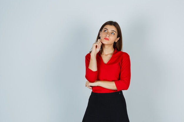 Young lady in red blouse, skirt standing in thinking pose and looking pensive