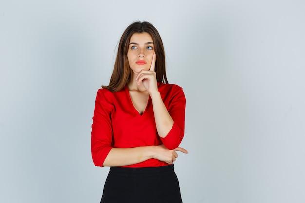 Giovane donna in camicetta rossa, gonna in piedi nella posa di pensiero e guardando pensieroso