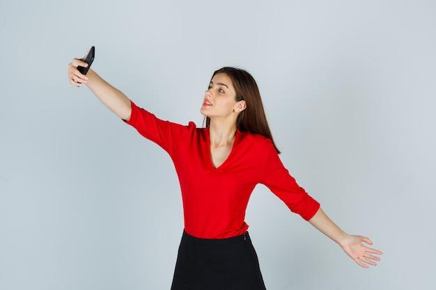 Giovane donna in camicetta rossa, gonna che prende selfie mentre allunga il braccio e sembra carina