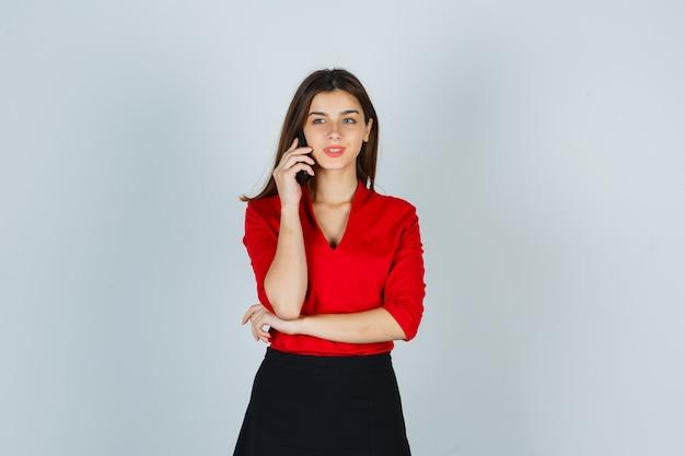 Giovane donna in camicetta rossa, gonna parlando al cellulare e guardando felice