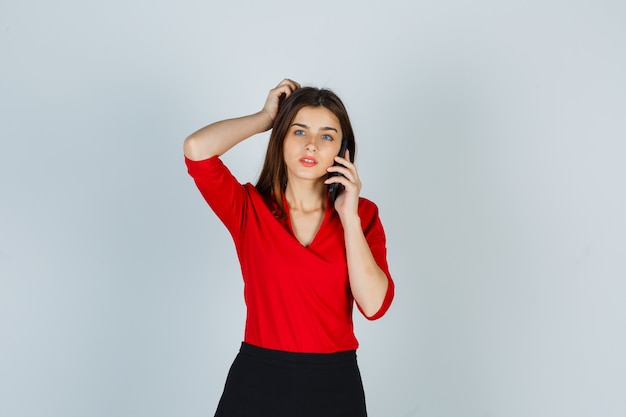 Giovane donna in camicetta rossa, gonna parlando al telefono cellulare