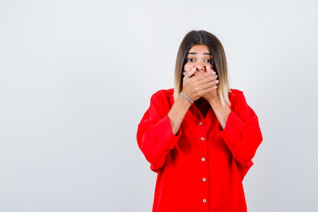 Young lady in red oversize shirt holding hands on mouth and looking puzzled , front view.