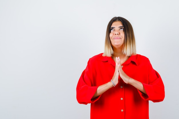 Young lady in red oversize shirt holding hands in praying gesture and looking hopeful , front view.