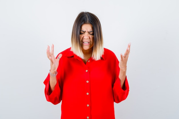 Young lady in red oversize shirt keeping hands in aggressive manner and looking annoyed , front view.