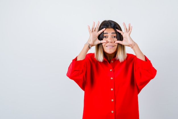 Giovane donna in camicia rossa oversize che apre gli occhi con le dita e sembra gioiosa, vista frontale.