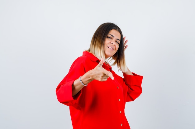 Young lady in red oversize shirt pointing aside and looking cheery , front view.