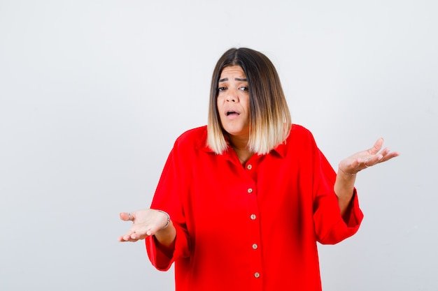Young lady in red oversize shirt showing helpless gesture and looking anxious , front view.