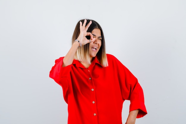 Young lady in red oversize shirt showing ok sign on eye and looking joyful , front view.