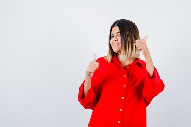 Giovane donna in camicia rossa oversize che mostra i pollici in su e sembra gioiosa, vista frontale.