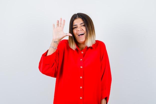 Giovane donna in camicia rossa oversize agitando la mano per salutare e sembrare gioiosa, vista frontale.