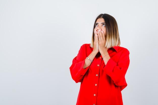 Giovane donna in camicia rossa oversize con le mani sulla bocca e con sguardo concentrato, vista frontale.