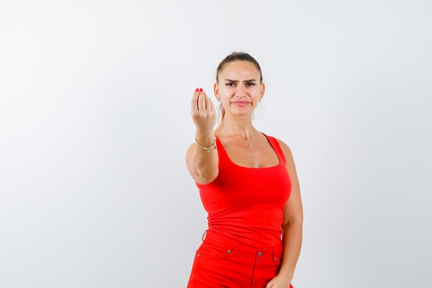 Young lady in red singlet, red trousers showing italian gesture and looking dissatisfied , front view.