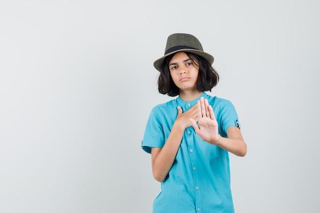 Giovane signora che rifiuta qualcosa in camicia blu, cappello e sguardo grato.