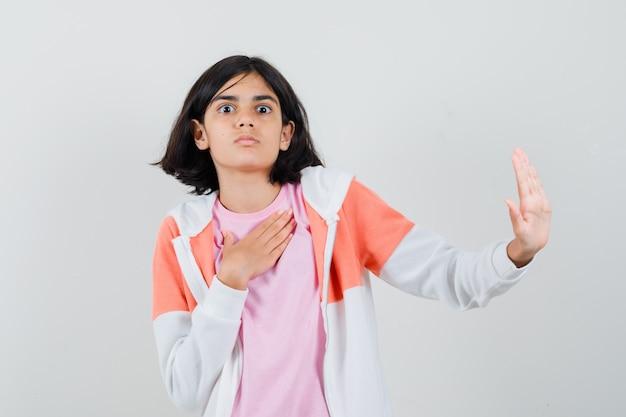 Giovane donna che rifiuta qualcosa in giacca, camicia rosa e sembra riluttante.
