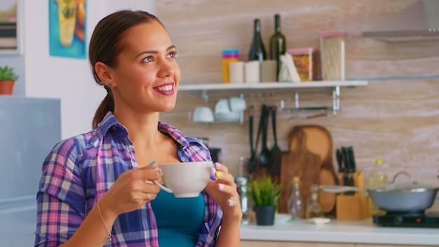Young lady relaxing with green tea in the morning sitting in the kitchen. dreamy happy woman looking away drinking morning herbal tea at home, smiling and holding cup enjoying with pleasant memories