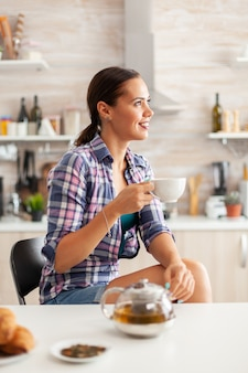 Young lady relaxing with green tea in the morning sitting in the kitchendreamy happy woman looking away drinking morning herbal tea at home, smiling and holding cup enjoying with pleasant memories
