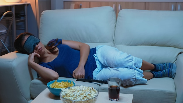 Young lady resting on sofa wearing mask for sleeping lying on cozy sofa. tired exhausted lonely sleepy woman in pajamas falling asleep on couch in front television, closing eyes while watching movie
