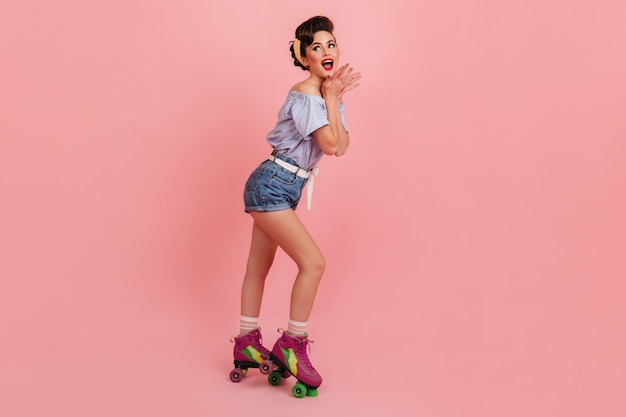 Young lady in roller skates screaming on pink background. studio shot of fashionable pinup girl.