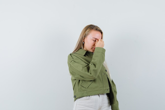 Young lady rubbing eyes and nose in jacket, pants and looking fatigued. front view.