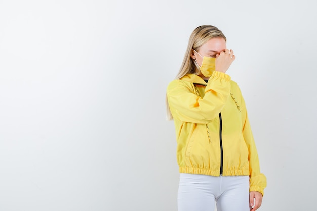 Young lady rubbing eyes and nose in jacket, pants, mask and looking fatigued , front view.