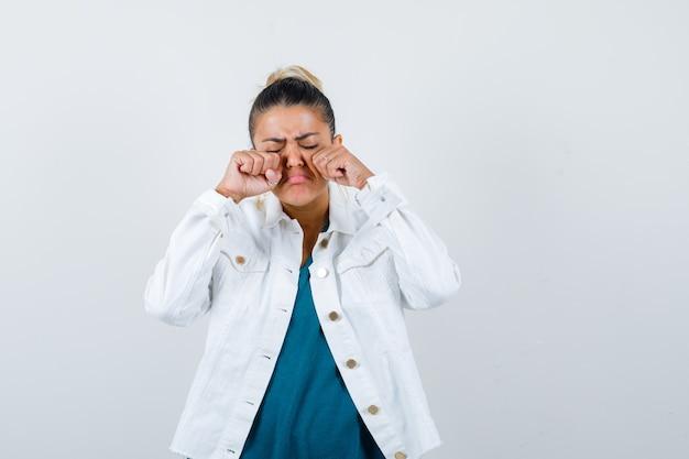 셔츠, 흰색 재킷을 입고 울고 슬픈 표정을 짓고 있는 젊은 여성이 눈을 비비고 있습니다.