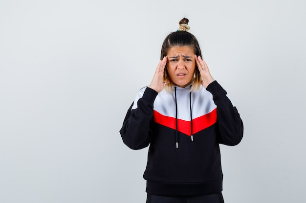 若い女性はパーカーのセーターで彼女の寺院をこすり、悲しそうに見えます。