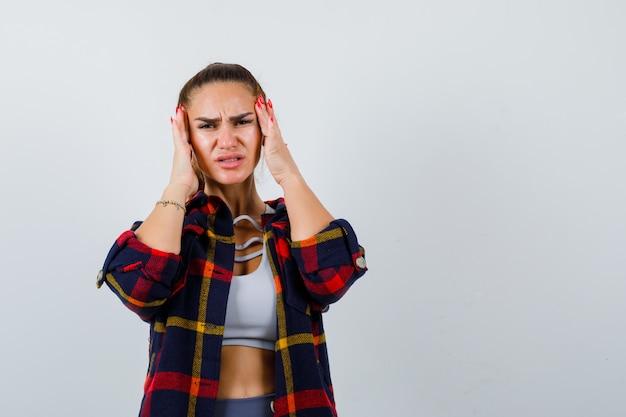 Giovane donna che si strofina le tempie in cima, camicia a quadri e sembra dolorante. vista frontale.