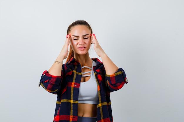 Giovane donna che si strofina le tempie in alto, camicia a quadri e sembra stressata, vista frontale.