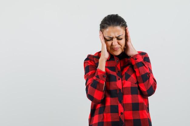 こめかみをこすり、チェックシャツで頭痛を持っている若い女性